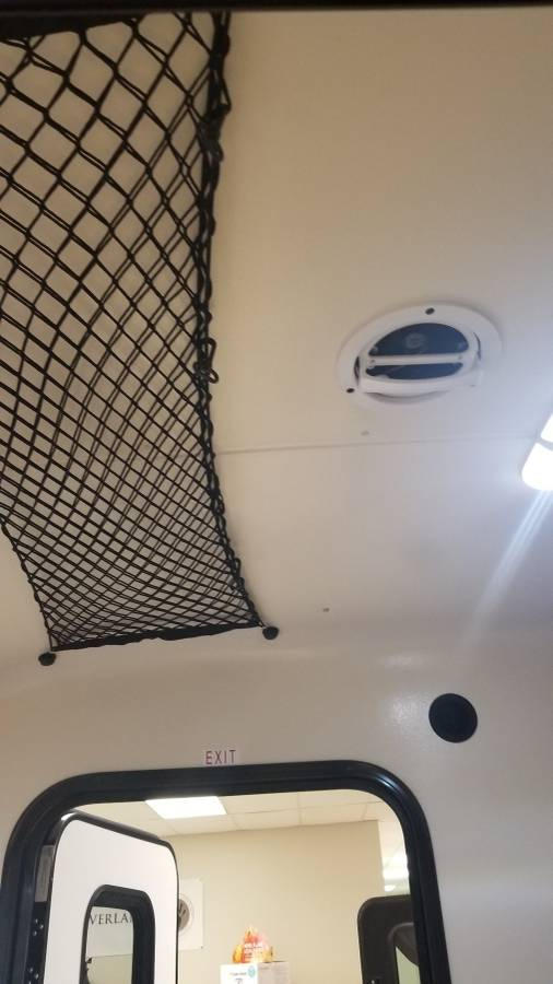 Interior stretchy storage net on ceiling of an Adventure camping trailer at Earthship Overland at their showroom in Englewood, CO
