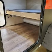 Interior view with pull-out bed inside an Adventure camping trailer at Earthship Overland at their showroom in Englewood, CO