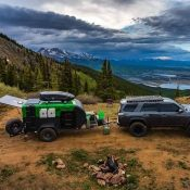 SUV pulling an Adventure camping trailer from Earthship Overland, with landscape of Colorado trees and mountains in background