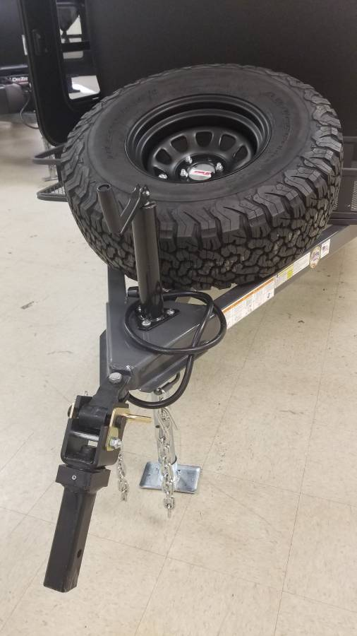 Spare tire and trailer hitch on the exterior of an Adventure camping trailer at Earthship Overland at their showroom in Englewood, CO