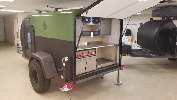 Open back hatch on the exterior of an Adventure camping trailer at Earthship Overland at their showroom in Englewood, CO