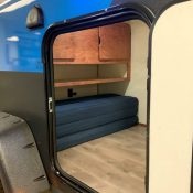 Interior view through open door of a blue Adventure camping trailer at Earthship Overland at their showroom in Englewood, CO