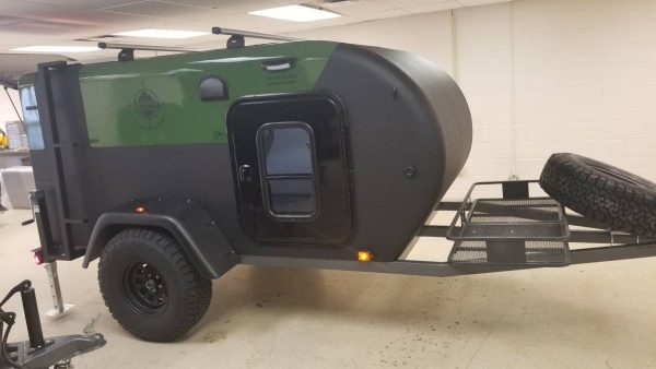 Side exterior view of an Adventure camping trailer at Earthship Overland at their showroom in Englewood, CO
