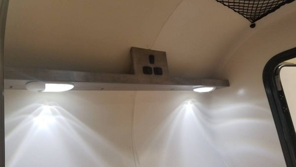 Ceiling lights and electrical outlet on interior of an Adventure camping trailer at Earthship Overland at their showroom in Englewood, CO