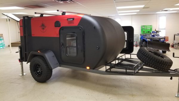 Side view of exterior of a red and black Adventure camping trailer at Earthship Overland at their showroom in Englewood, CO