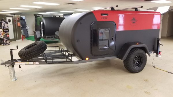 Side view exterior of a red and black Adventure camping trailer at Earthship Overland at their showroom in Englewood, CO