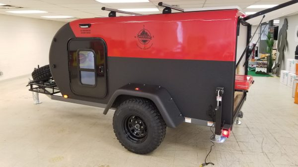Exterior side view of an Adventure camping trailer with open back hatch, at Earthship Overland at their showroom in Englewood, CO
