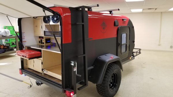 Exterior view of a red Adventure camping trailer with open hatchback area, at Earthship Overland at their showroom in Englewood, CO