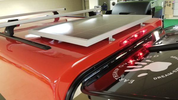 Top exterior and solar panel on a red Adventure camping trailer at Earthship Overland at their showroom in Englewood, CO