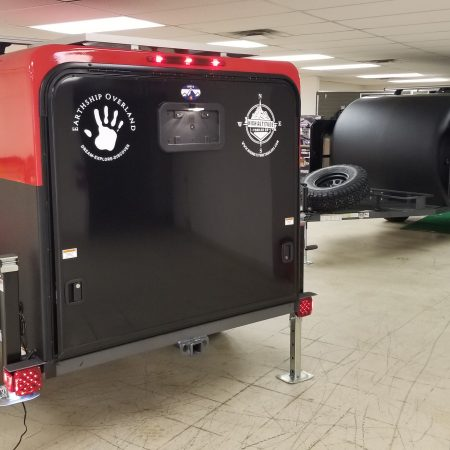 Rear exterior view of a red and black Adventure camping trailer at Earthship Overland at their showroom in Englewood, CO