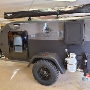 Side view exterior of an Adventure camping trailer at Earthship Overland at their showroom in Englewood, CO