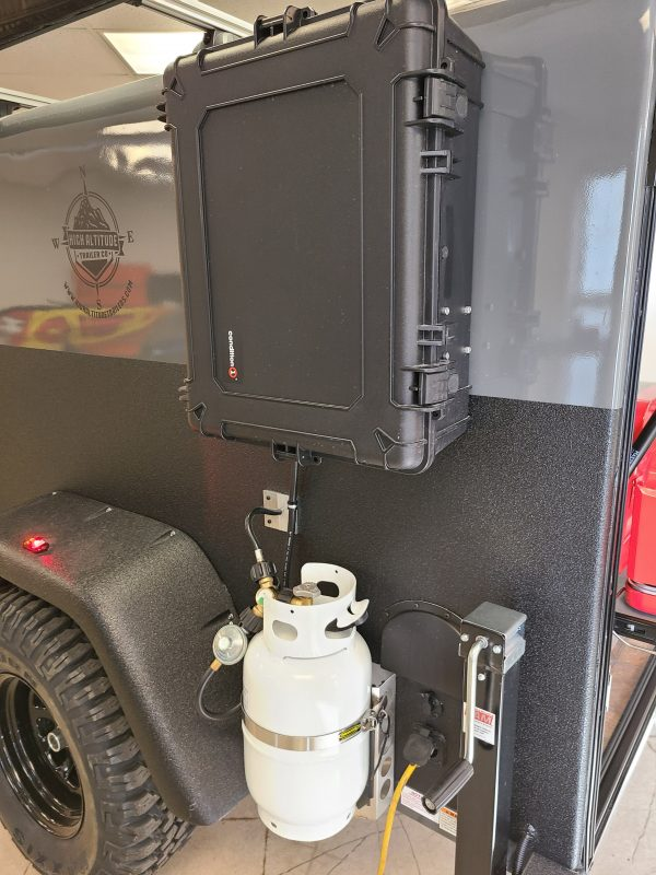 Propane tank and black plastic box attached to exterior of an Adventure camping trailer at Earthship Overland at their showroom in Englewood, CO