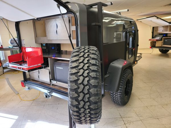 Back of an Adventure camping trailer outfitted with collapsible grill at Earthship Overland at their showroom in Englewood, CO