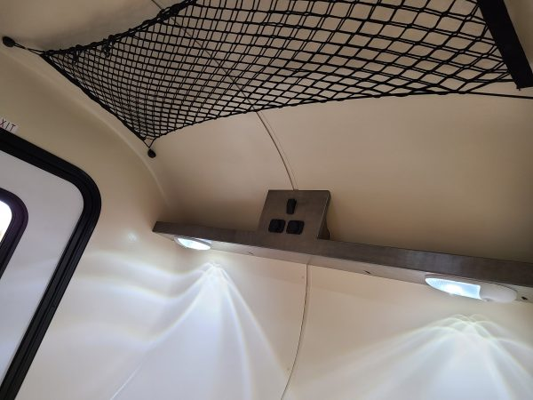 Storage net on ceiling of the interior of an Adventure camping trailer at Earthship Overland at their showroom in Englewood, CO