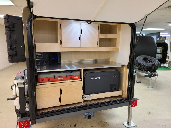 Open back of an Adventure camping trailer featuring storage and kitchen type area. In showroom at Earthship Overland in Englewood, CO